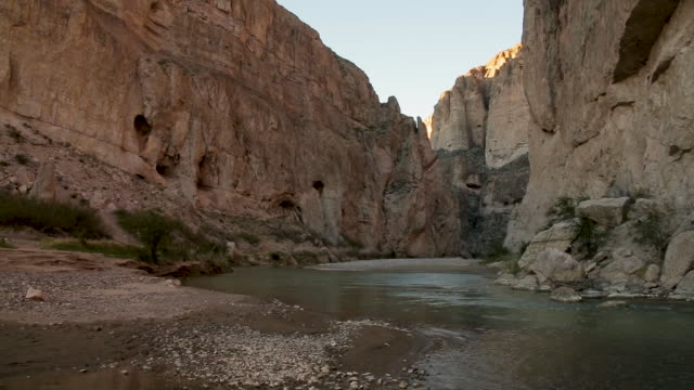 River flows through a desert canyon, crane falls