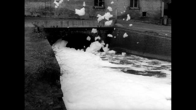 river flows through city covered in white foam; 1963 - 1963 stock videos & royalty-free footage
