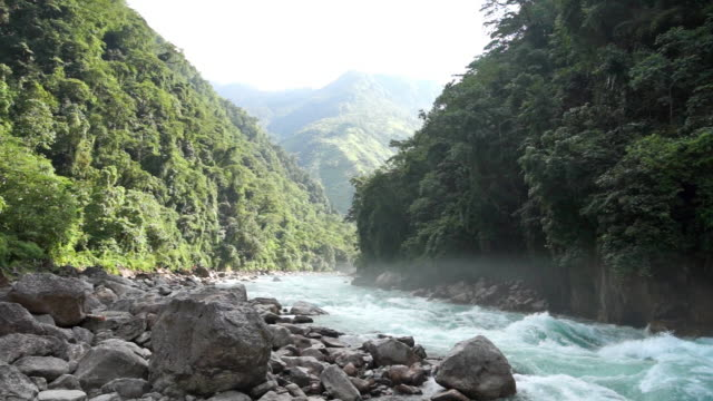 a river flows through the jungle in khakaborazi national park  - myanmar stock videos & royalty-free footage