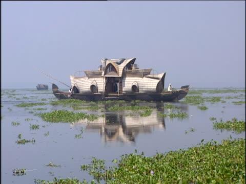 vídeos de stock e filmes b-roll de river houseboat slowly sailing along calm river amongst reeds; kerala - barco casa