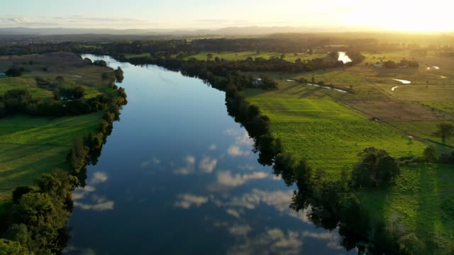 river landscape with reflection of blue sky at sunset - sunbeam stock videos & royalty-free footage