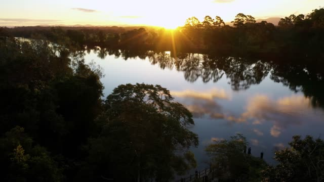 river landscape with trees and reflection of blue sky and clouds at sunset - sunbeam stock videos & royalty-free footage