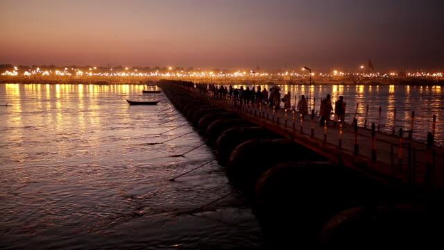 river, like molten silver, flows under pontoon bridge as kumbh mela pilgrims cross, many carrying possessions on head.  flights of swallows. india - pontoon bridge stock videos and b-roll footage