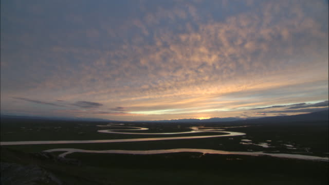 River meanders through grassland at sunset, Bayanbulak grasslands.