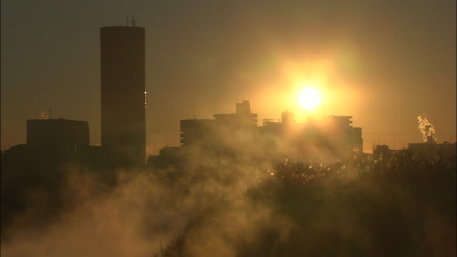 River mist rises and glows in morning sun with tall buildings in distance