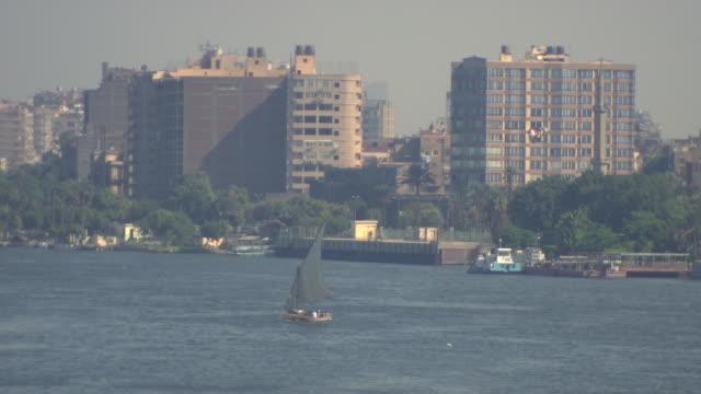 river nile, cairo - sailboat moving downstream - ダウ船点の映像素材/bロール