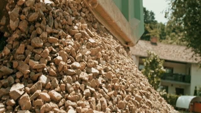 slo mo river of stones running from the truck unloading them in sunshine - pietra materiale da costruzione video stock e b–roll