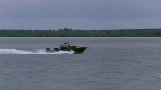 ts river patrol boat speeding across the mekong delta waters / vietnam - vagare senza meta video stock e b–roll