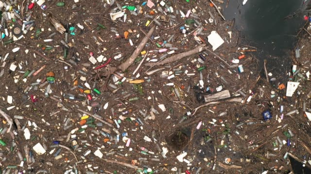 river polluted with garbage - floating on water stock videos & royalty-free footage