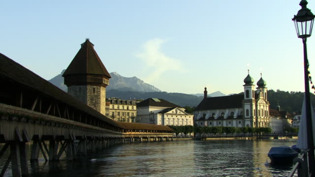 ms, river reuss with chapel bridge and water tower, jesuit church in distance, lucerne, switzerland - circa 14th century stock videos & royalty-free footage