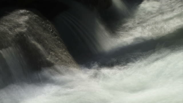a river roars and splashes through boulders. - digital enhancement stock videos and b-roll footage