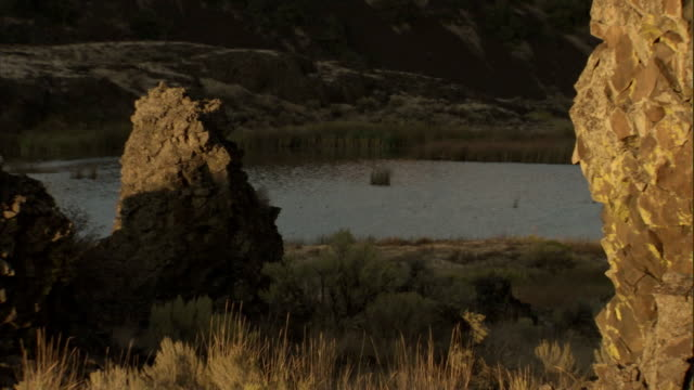 A river runs past the base of large rock formations in the Scablands. Available in HD.