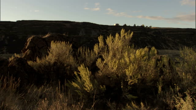 A river runs past the large rock formations and dry hills of the Scablands. Available in HD.