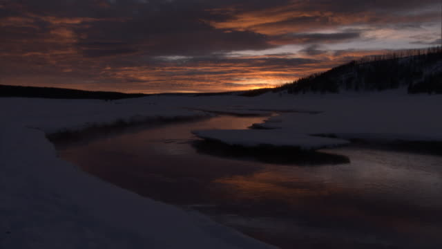 river runs through snowy landscape at sunrise, yellowstone, usa - river yellowstone stock videos and b-roll footage