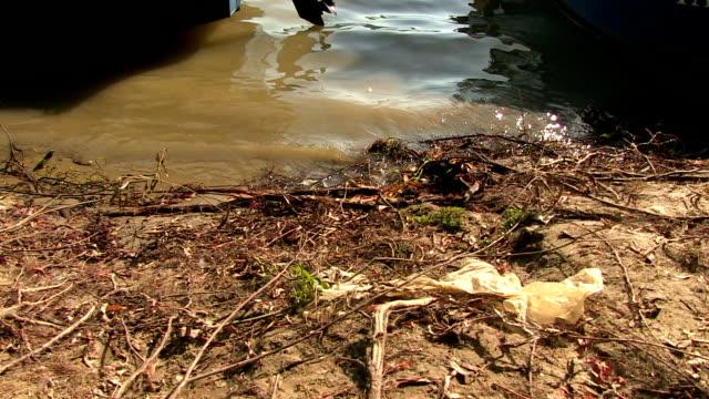 vídeos de stock, filmes e b-roll de margem do rio - saco de lixo