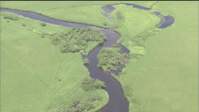 vídeos y material grabado en eventos de stock de a river snakes through the lush kushiro marsh in japan - río snake