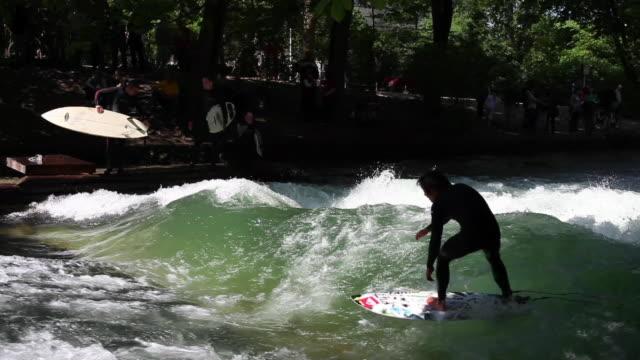 river surfer on eisbach in munich - ミュンヘン エングリッシャーガルテン点の映像素材/bロール
