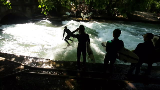 river surfers on eisbach in munich - munich stock videos & royalty-free footage
