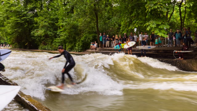 TL ZO River surfers on the river Isar in the English Garden in Munich