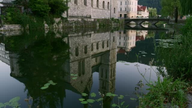 vidéos et rushes de rivière tu entourant l'église à kocevje - pierre
