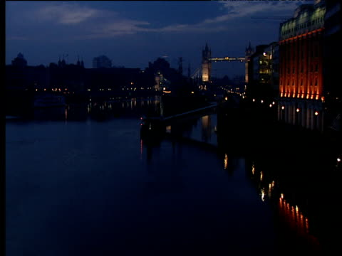 river thames at night tower bridge in distance illuminated buildings either side - coastal feature stock videos & royalty-free footage