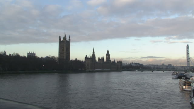 River Thames reflects Victoria Tower and the Houses of Parliament on a cloudy day in London, England.