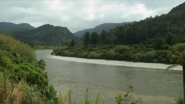 ws river valley amid lush green hills / murchison, new zealand - new zealand stock-videos und b-roll-filmmaterial