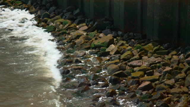 River water splashes on rocks along a concrete wall