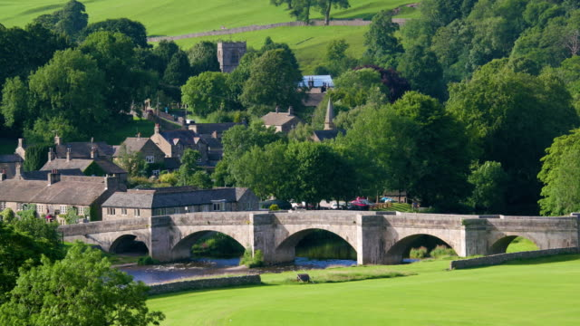 river wharfe bridge & village burnsall, north yorkshire, england - bandiera inglese video stock e b–roll