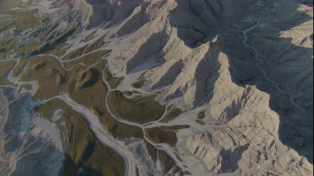 riverbeds snake around the base of south dakota's rugged badlands. available in hd. - badlands national park stock videos & royalty-free footage