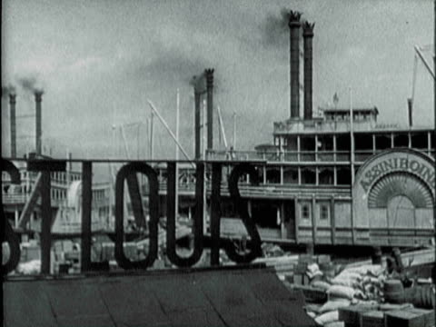 stockvideo's en b-roll-footage met montage riverboats docked and men loading burlap sacks onto dock / st. louis, missouri, united states - korrelig