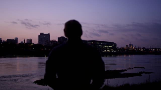 夕暮れ時のリバーサイド。バック グラウンドで都市のスカイライン。景色を眺めながらの男 - 都市景観点の映像素材/bロール