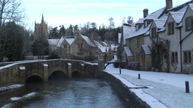 ws riverside houses in snow / castle coombe, wiltshire, england - stationary process plate stock videos and b-roll footage