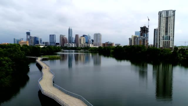 vídeos de stock e filmes b-roll de riverside pedestrian bridge mirrored reflections of downtown skyline cityscape town lake - town