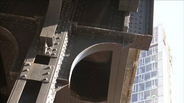 riveted steel girders support a bridge deck. - trave intelaiatura video stock e b–roll