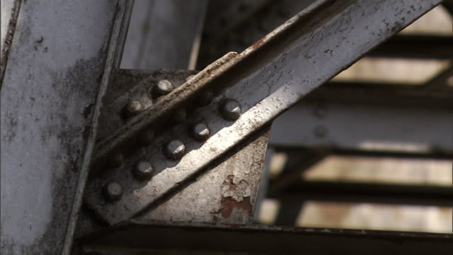 rivets line the rusty framework of a railway trestle in kenya. - railway bridge stock videos & royalty-free footage