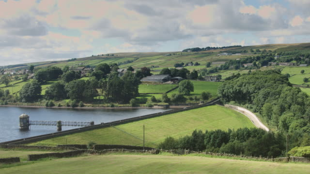 vídeos de stock e filmes b-roll de road across dam surrounded by farmland - feito pelo homem