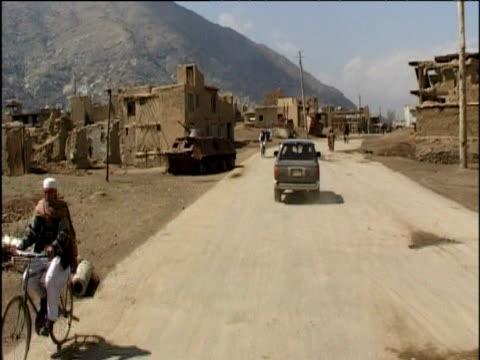 Road and market scenes in Kabul during Taliban rule including women in burkha and soldier with rifle