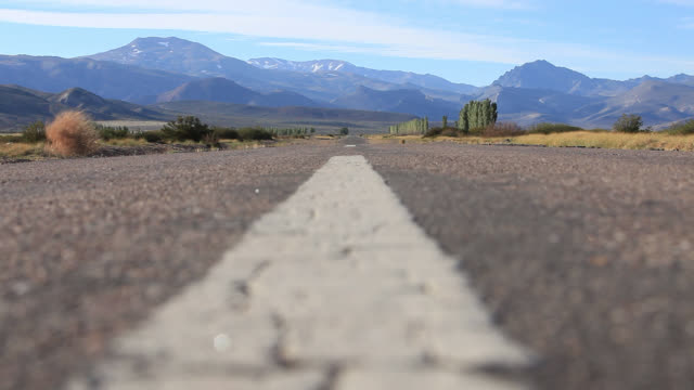 Road and Mountains with tumbleweed in rural Argentina