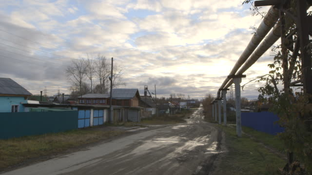 road and pipeline run through village of asbest under cloudy sky, wide shot - asbest stock-videos und b-roll-filmmaterial