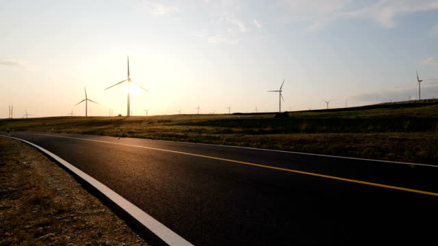 road and wind turbines at sunset - sustainable resources stock videos & royalty-free footage
