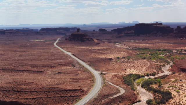 road approaching monument valley - aerial shot - native american reservation stock videos & royalty-free footage