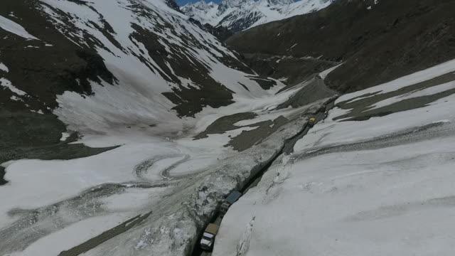 road at base of snowy mountain - gebäudefries stock-videos und b-roll-filmmaterial