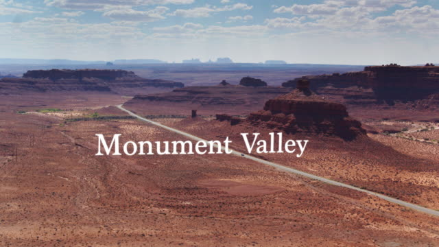 road between buttes in monument valley - drone shot with floating text - navajo reservation stock videos and b-roll footage