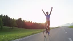 SLOW MOTION: Road biker happy to finish challenging race in golden-lit nature.