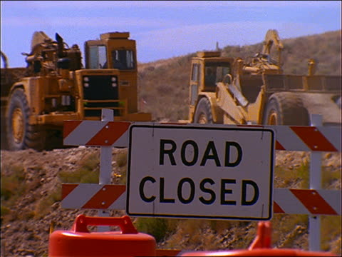 """road closed"" sign with heavy equipment passing in background (road construction) - road construction stock videos and b-roll footage"