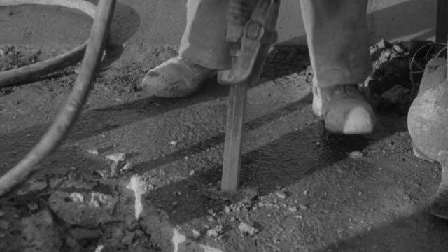 montage road construction crew with jackhammer digging up old pavement and worker guiding trolley of new fill dirt into position before pouring / united kingdom - digging stock videos & royalty-free footage