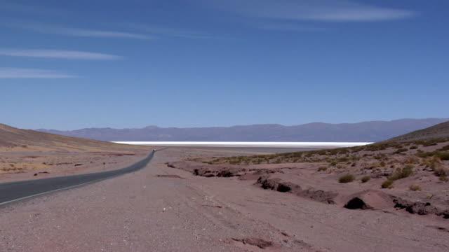 WS ZO Road crossing desert landscape, track in distance, San Pedro de Atacama, El Loa, Chile