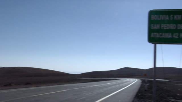 ws pan road crossing desert landscape with bolivia, sao pedro do atacama sign and volcano in background, san pedro de atacama, el loa, chile - san pedro de atacama stock videos & royalty-free footage
