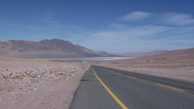 ws zi road crossing desert landscape with lagoon and mountains, san pedro de atacama, el loa, chile - san pedro de atacama stock videos & royalty-free footage